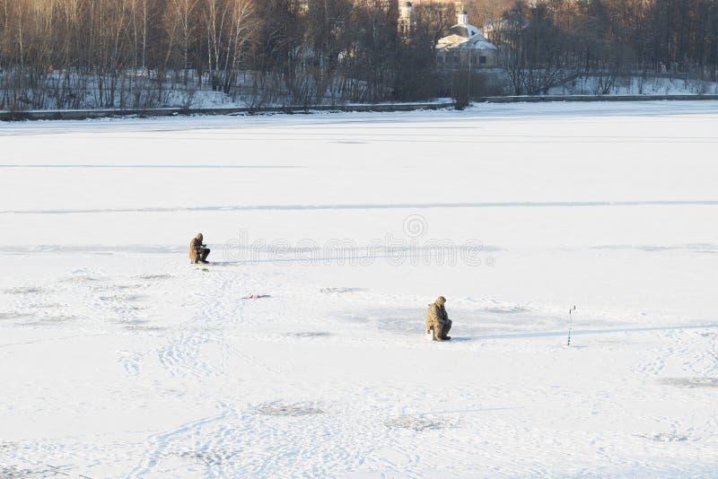 Pescadores en el hielo nevoso en el río imágenes de archivo libres de regalías