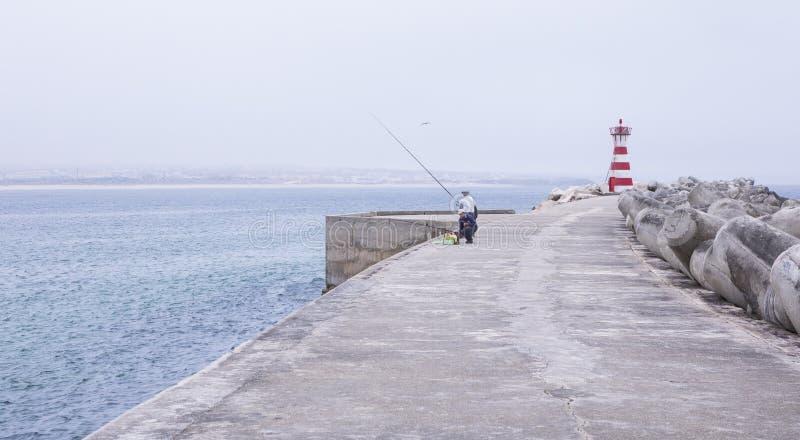 Pescadores en el malecón y el rompeolas en el faro en el puerto de Peniche, Portugal imágenes de archivo libres de regalías