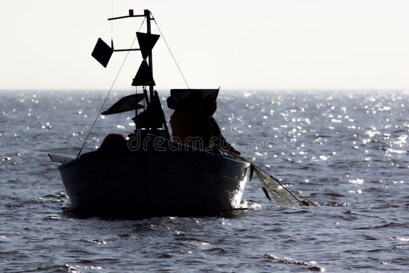 Pescadores en el mar que tira en la red de un pequeño barco de pesca foto de archivo