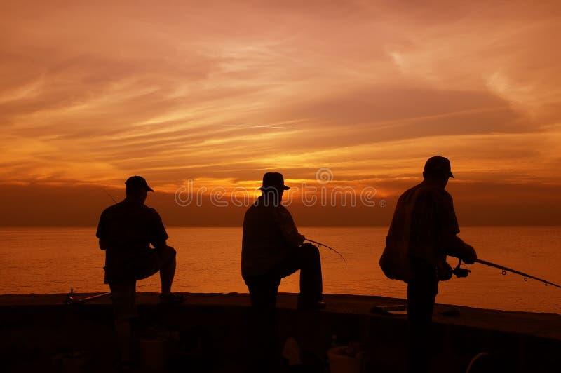 Pescadores en la puesta del sol fotografía de archivo