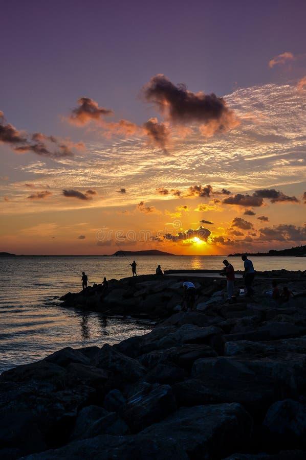 Pescadores en puesta del sol imagen de archivo