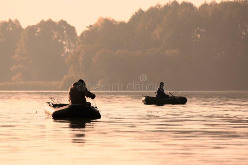 Pescadores en un pescado de cogida del barco temprano por la mañana imagen de archivo
