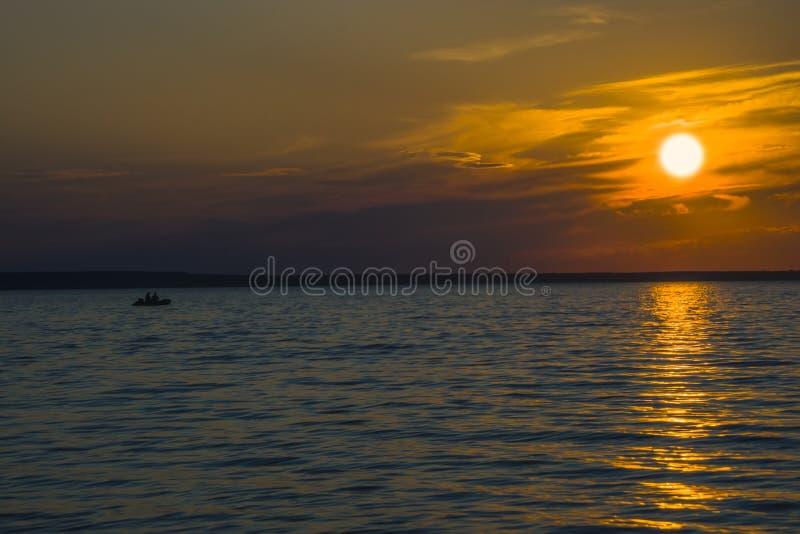 Pescadores no barco no lago no fundo do por do sol foto de stock