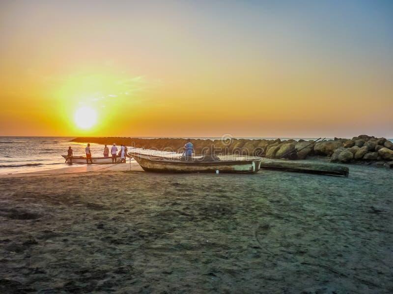 Pescadores no por do sol na praia em Cartagena fotos de stock royalty free