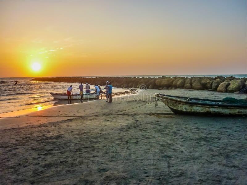 Pescadores no por do sol na praia em Cartagena imagens de stock royalty free