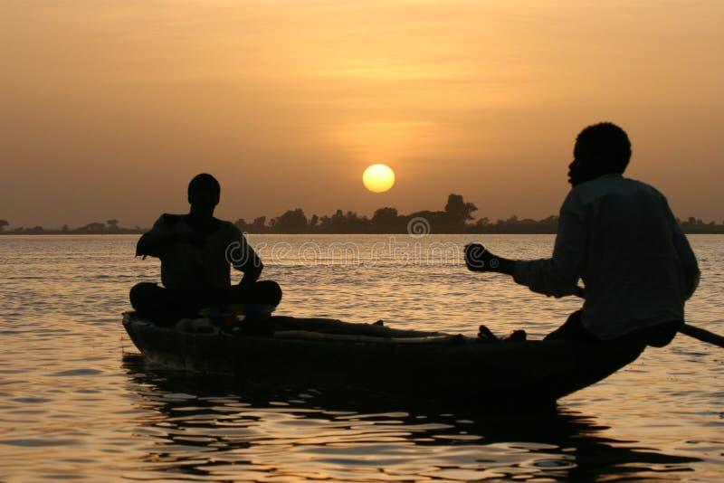 Pescadores que cruzan un lago en la puesta del sol imagenes de archivo