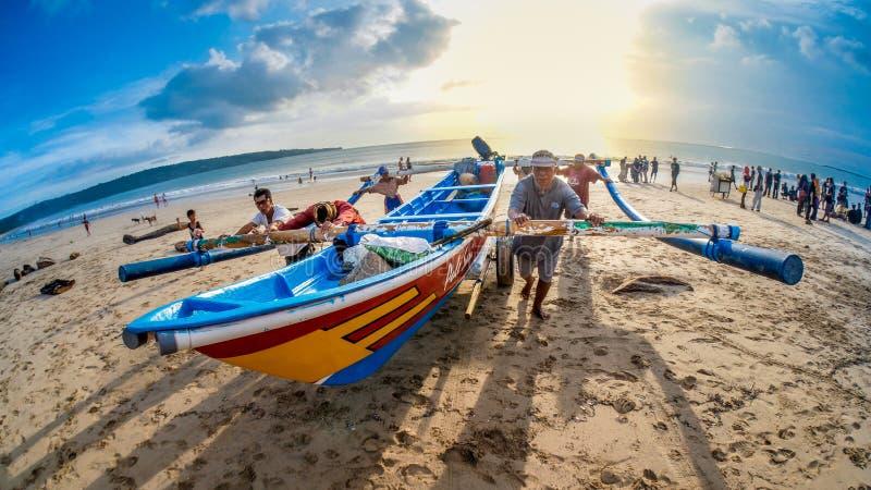 Pescadores que empujan el barco de pesca junto en Jimbaran Bali imagen de archivo libre de regalías