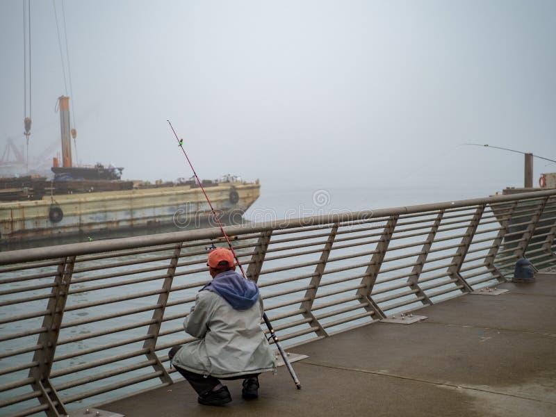 Pescadores que examinam a captura no cais industrial no dia nevoento fotografia de stock