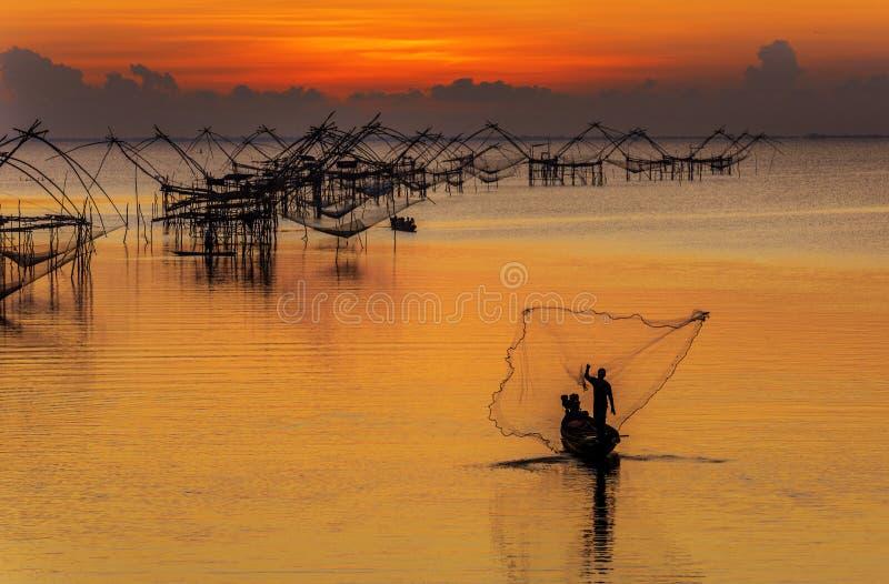 Pescadores que jogam a rede de pesca de seu amanhecer do barco fotografia de stock