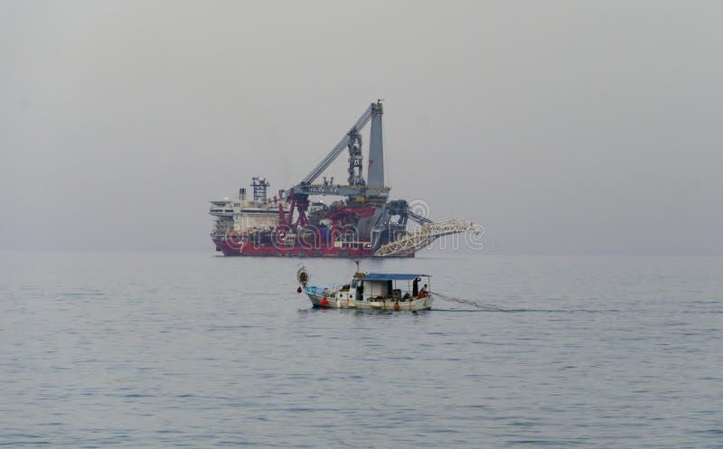 Pescadores que lanzan redes de pesca contra la nave moderna fotografía de archivo libre de regalías