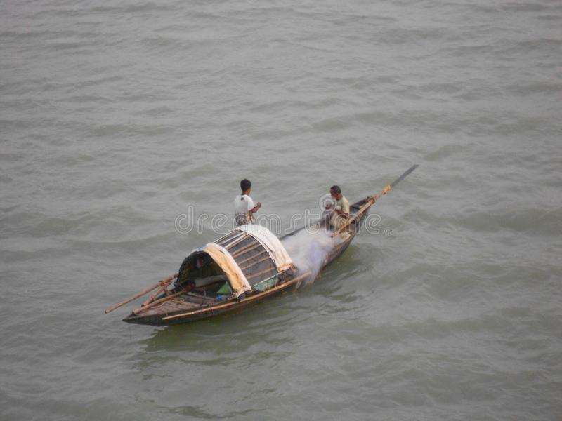 Pescadores que montam no rio com barco de pesca foto de stock