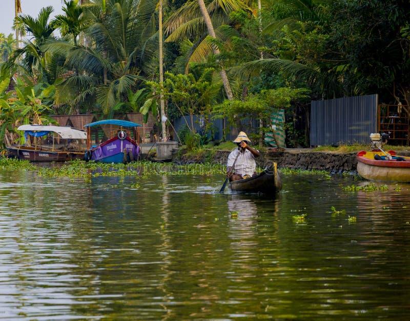 Pescadores que reman un barco para su trabajo diario en los remansos del alleppey en Kerala fotografía de archivo