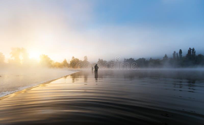 Pescadores que sostienen la caña de pescar, colocándose en el río imagen de archivo