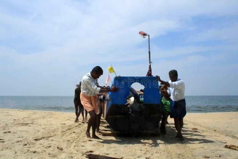 Pescadores que traen su barco a la orilla imágenes de archivo libres de regalías