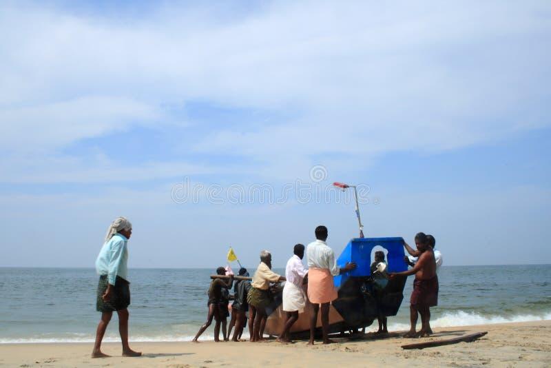 Pescadores que traen su barco a la orilla fotografía de archivo libre de regalías
