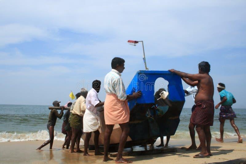 Pescadores que traen su barco a la orilla foto de archivo