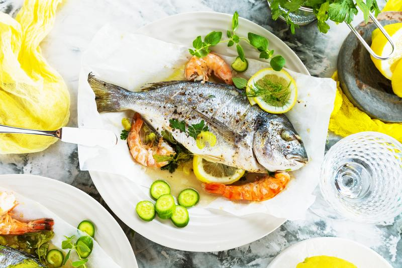 Pescados asados deliciosos de la brema del dorado o de mar con el limón y las gambas frescas imagenes de archivo