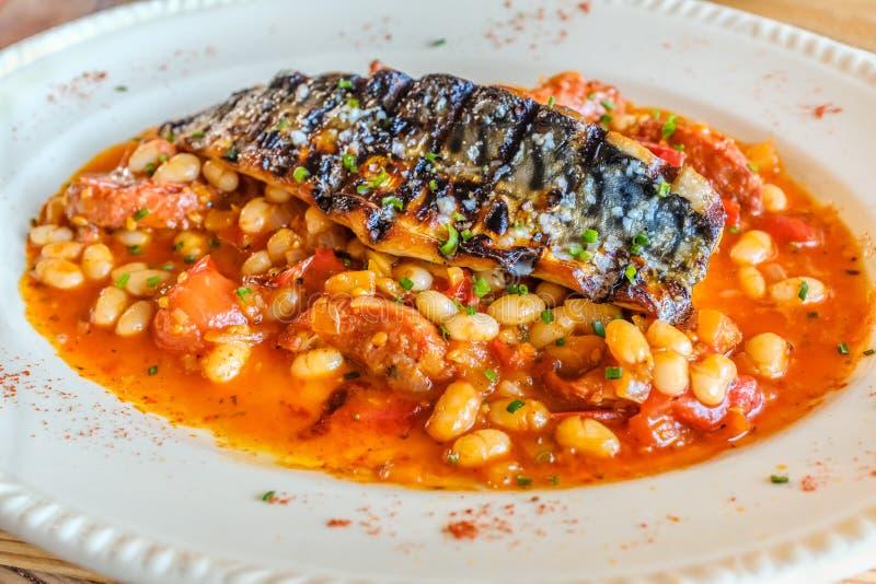 Pescados asados a la parrilla de la caballa en una salsa picante del tomate y del chorizo y de la judía en una placa oval blanca imagen de archivo libre de regalías