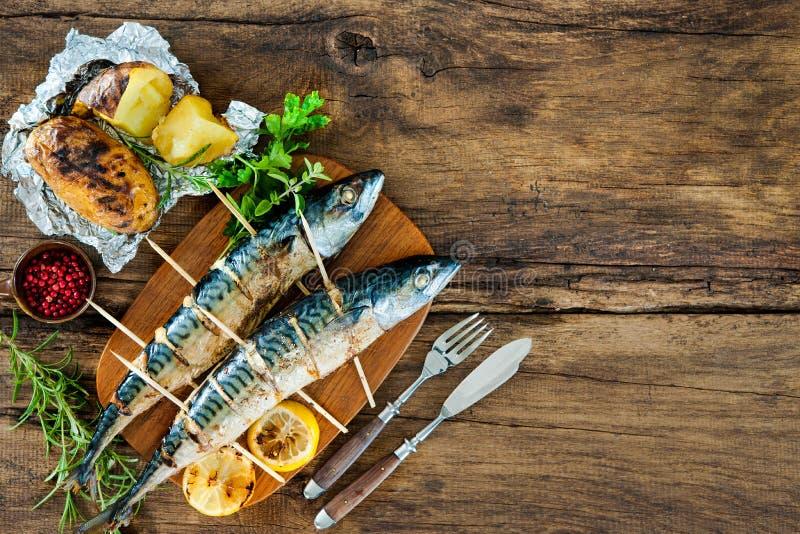 Pescados asados a la parrilla de la caballa con las patatas cocidas foto de archivo