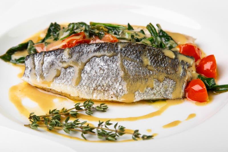 Pescados blancos con las verduras en salsa ligera en la placa cuadrada en whi foto de archivo