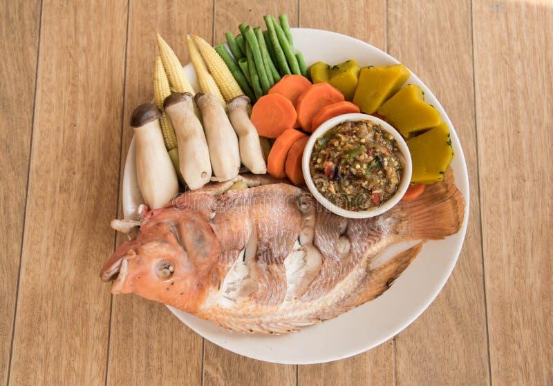 Pescados cocidos al vapor y verduras de la Tilapia del Nilo, servidos con la salsa fotografía de archivo libre de regalías