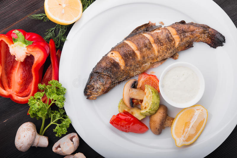 Pescados cocidos con el limón y las verduras asadas a la parrilla fotografía de archivo