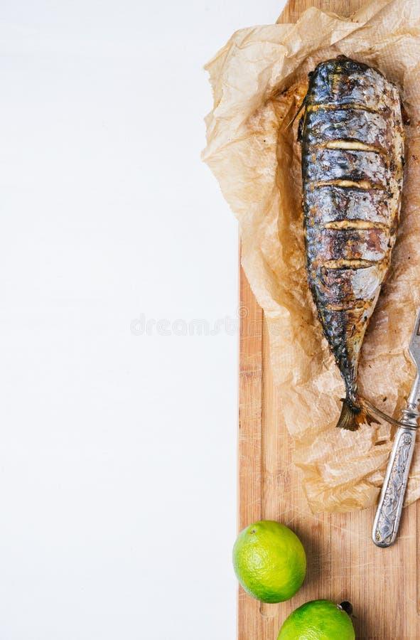 Pescados cocidos con las verduras y la cal asadas en el papel de pergamino y tabla de cortar en un fondo blanco de viejos tablero fotografía de archivo libre de regalías