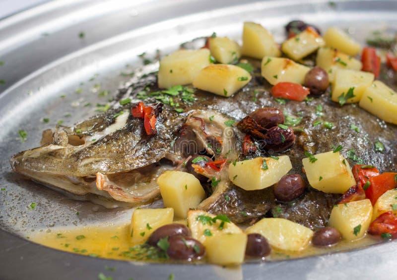 Pescados cocidos de la platija con las patatas, las aceitunas y los tomates fotos de archivo
