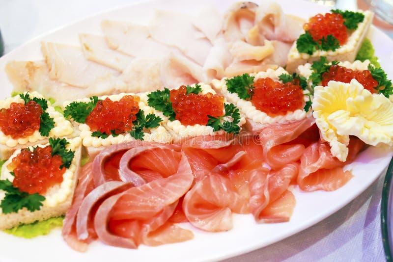 Pescados cortados y cesta cocida con el caviar rojo en una placa en un restaurante imagenes de archivo