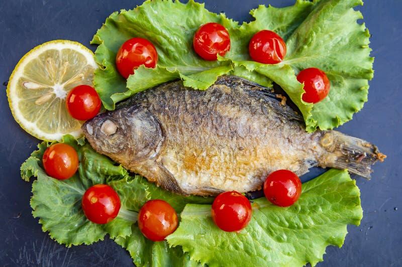 Pescados crucian fritos en un fondo negro con las verduras y el limón imágenes de archivo libres de regalías