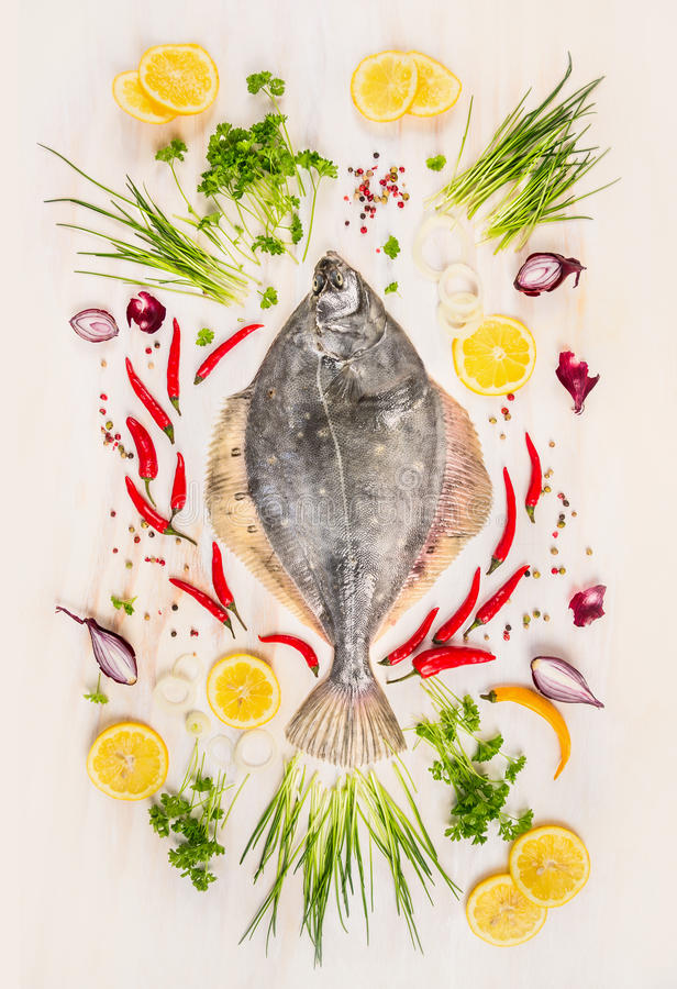 Pescados crudos de la platija con el condimento, el limón y las especias frescos encendido con el fondo de madera rústico imagen de archivo libre de regalías