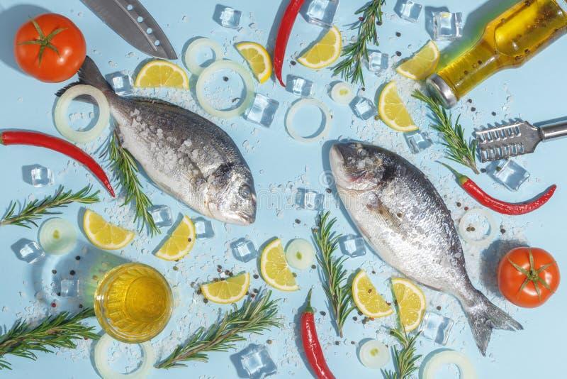 Pescados crudos del dorada con las especias, la sal, el limón y las hierbas, romero en un fondo ligth-azul Visión superior foto de archivo