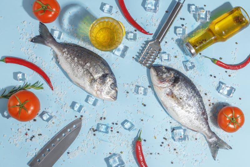 Pescados crudos del dorada con las especias, la sal, el limón y las hierbas, romero en un fondo ligth-azul Visión superior imagen de archivo libre de regalías