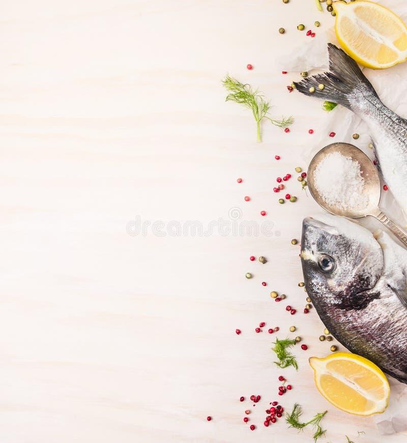 Pescados crudos del dorado con la pimienta multicolora, limón una cuchara de la sal en el fondo de madera blanco, visión superior imagen de archivo libre de regalías