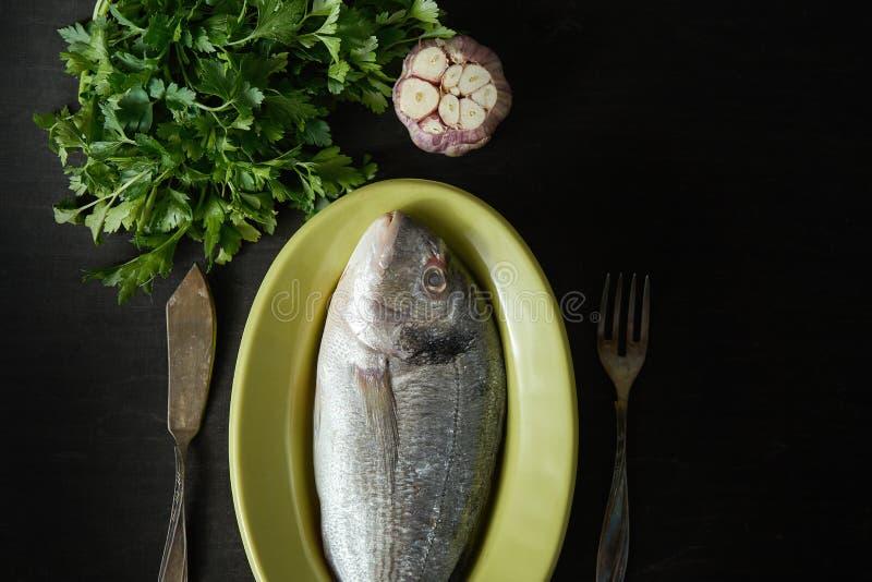Pescados crudos frescos del dorada en un plato verde con perejil y ajo, la bifurcación y el cuchillo en una tabla negra imagenes de archivo