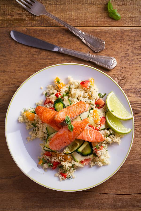 Pescados de color salmón asados con cuscús, el calabacín y la cal del tomate en la placa blanca fotos de archivo