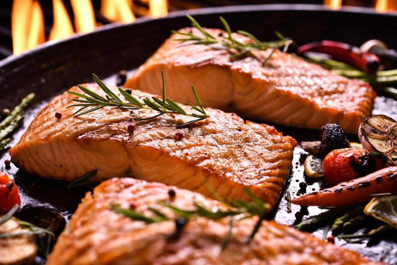 Pescados de color salmón asados a la parrilla con las diversas verduras en la cacerola fotografía de archivo libre de regalías