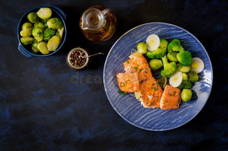 Pescados de color salmón cocidos adornados con bróculi y las coles de Bruselas con el puerro fotos de archivo