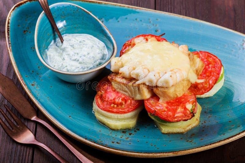 Pescados de color salmón cocidos con el camarón, el queso, los tomates, la berenjena y la salsa en fondo de madera imágenes de archivo libres de regalías