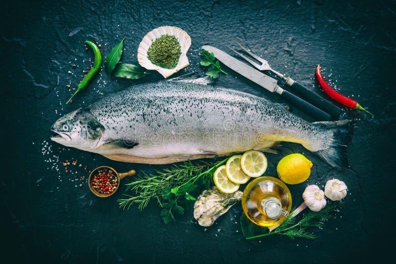 Pescados de color salmón frescos con el condimento en piedra negra foto de archivo libre de regalías