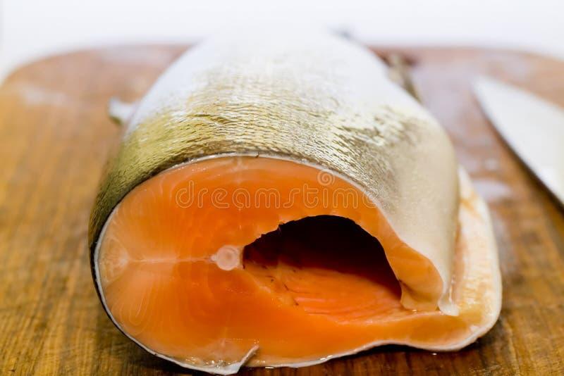 Pescados de color salmón frescos con el cuchillo en el escritorio de cocinar de madera imágenes de archivo libres de regalías