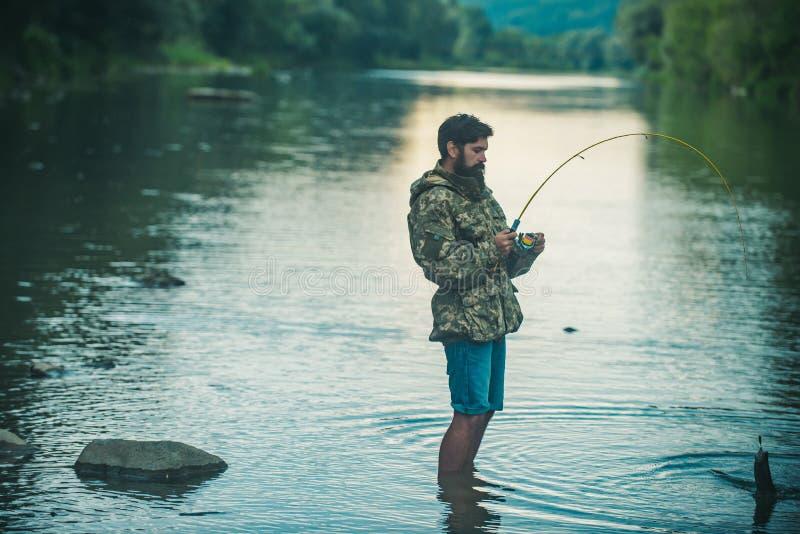 Pescados de la captura Sostener la trucha marrón Retrato de la pesca alegre del hombre angler foto de archivo