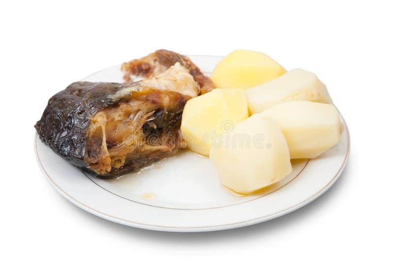 Pescados de la carpa con las patatas en la placa blanca imagenes de archivo