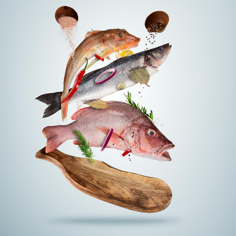 Pescados de mar frescos con las especias que caen, volando sobre el tablero de madera libre illustration