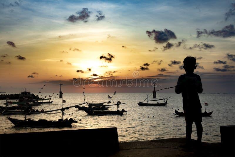 Pescados del niño pequeño en un embarcadero en un puerto rústico Silueta de un muchacho en la puesta del sol, sosteniendo trole y foto de archivo