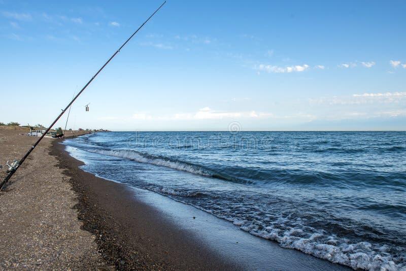Pescados del pescador temprano por la mañana en la orilla Caña de pescar y giro camping fotos de archivo