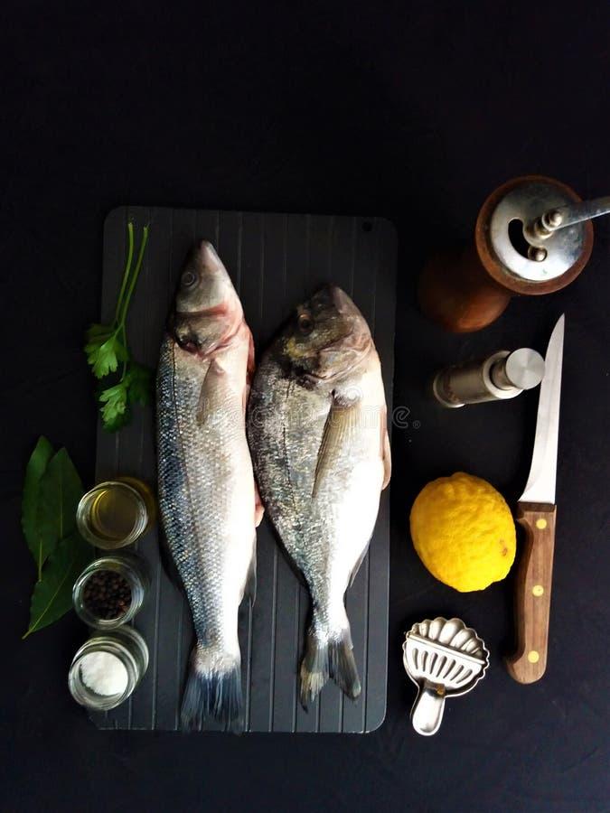 Pescados frescos con el lim?n y las especias foto de archivo