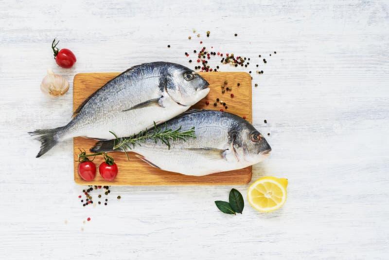 Pescados frescos crudos del dorada con las verduras y las especias Concepto sano del alimento Visión superior, espacio de la copi fotos de archivo