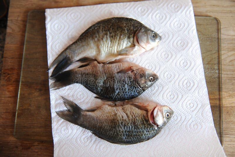 Pescados frescos crudos enteros en tablero cortado El proceso de cocinar foto de archivo