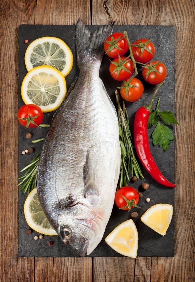 Pescados frescos, limón, especias y tomates de cereza en un tablero de piedra fotografía de archivo libre de regalías